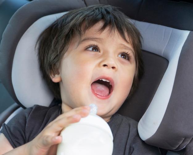 Menino bonitinho bebendo garrafa de leite em um assento de carro enquanto viaja