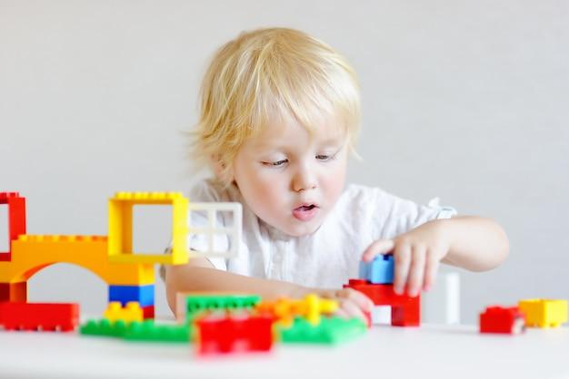 Menino bonitinho brincando com blocos de plástico coloridos dentro de casa