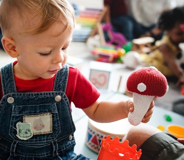Menino bonitinho brincando com brinquedos no centro de aprendizagem