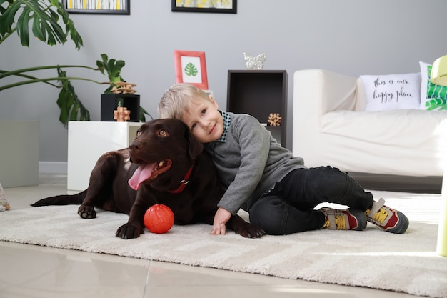 Menino bonitinho brincando com cachorro engraçado em casa