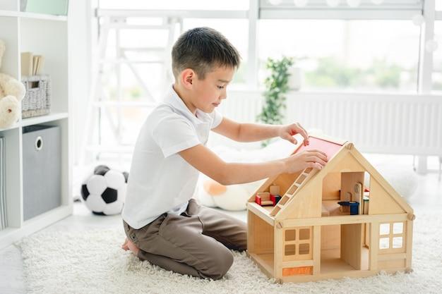 Menino bonitinho brincando com casa de boneca
