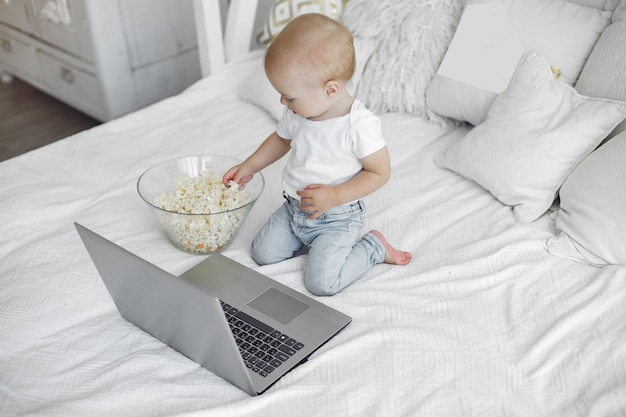 Menino bonitinho brincando com um laptop em uma cama