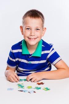 Menino bonitinho brincando enigmas na mesa