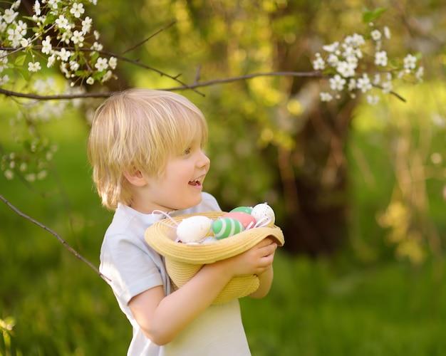 Menino bonitinho caça ovo de páscoa no parque primavera.