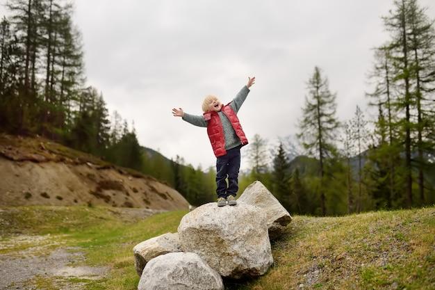 Menino bonitinho caminha no parque nacional da suíça na primavera. caminhadas com crianças pequenas.