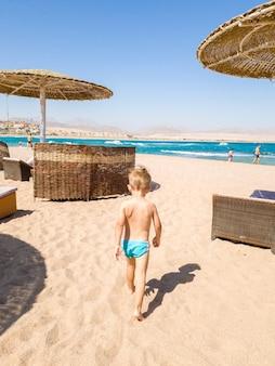 Menino bonitinho caminhando para o mar e olhando as ondas do oceano. criança relaxando e se divertindo durante as férias de férias de verão.