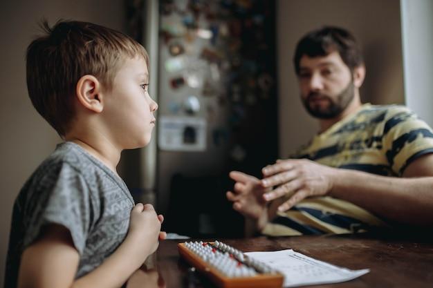 Menino bonitinho caucasiano fazendo sua lição de casa de aritmética mental com o pai sentado ao lado dele na mesa da cozinha. foto de alta qualidade