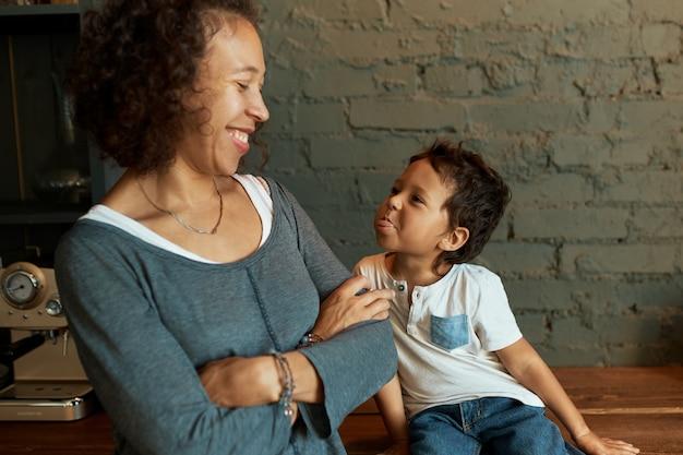 Menino bonitinho com a língua de fora, sua linda jovem mãe sorrindo amplamente, se divertindo juntos