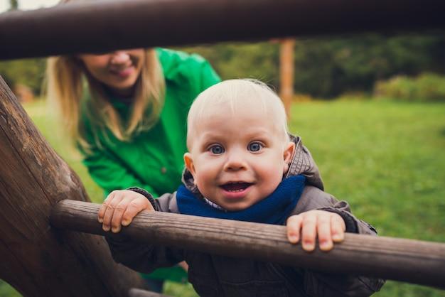 Menino bonitinho com a mãe brincar ao ar livre