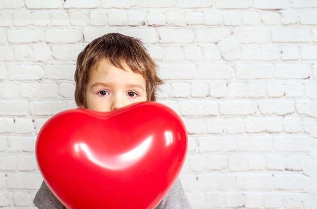 Menino bonitinho com balão em forma de coração vermelho no fundo da parede de tijolos brancos, plano de fundo do dia dos namorados