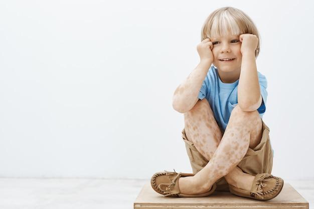 Menino bonitinho com cabelo loiro e manchas na pele, sentado com os pés cruzados, segurando as mãos perto do rosto e sorrindo com uma expressão alegre e despreocupada, olhando para o lado