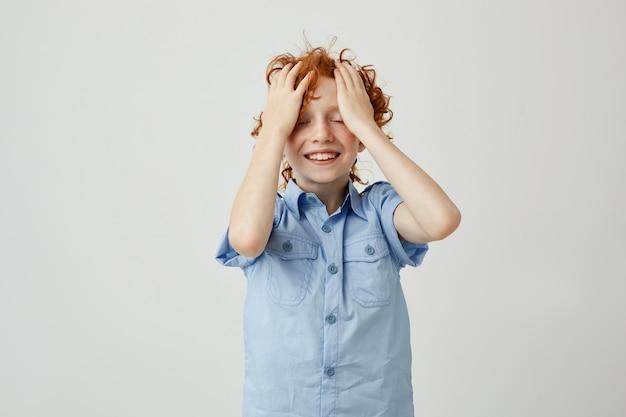 Menino bonitinho com cabelos ondulados vermelhos e olhos fechados, segurando as mãos na testa