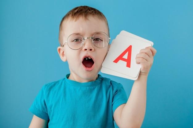 Menino bonitinho com carta na parede azul. criança aprendendo letras. alfabeto