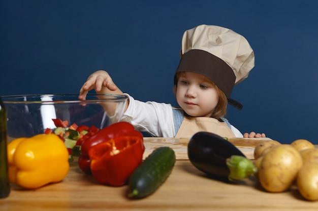 Menino bonitinho com chapéu de chef em pé à mesa da cozinha