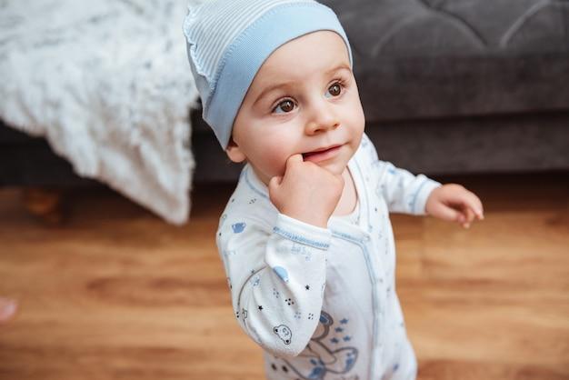 Menino bonitinho com chapéu em pé em casa