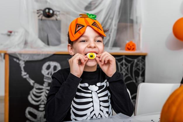 Menino bonitinho com fantasia assustadora, apreciando seus doces de halloween. jack o 'lantern abóbora de halloween na mesa e outras decorações assustadoras