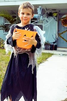 Menino bonitinho com fantasia de esqueleto de halloween menino com fantasia de esqueleto com balde de doces de abóbora