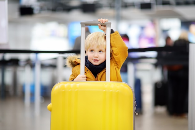 Menino bonitinho com grande mala amarela no aeroporto internacional antes do voo