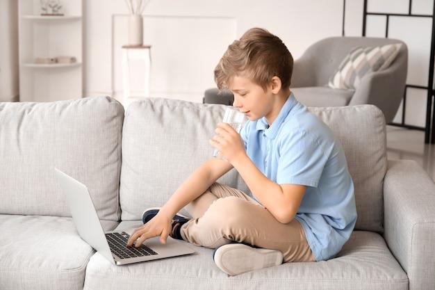 Menino bonitinho com laptop bebendo água em casa