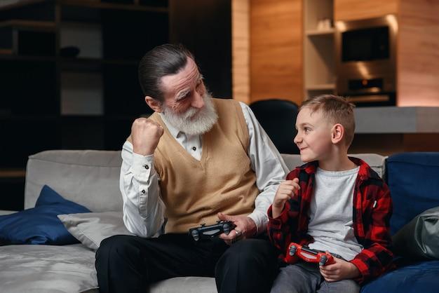 Menino bonitinho com o avô sentado no sofá e jogando videogame com game pad