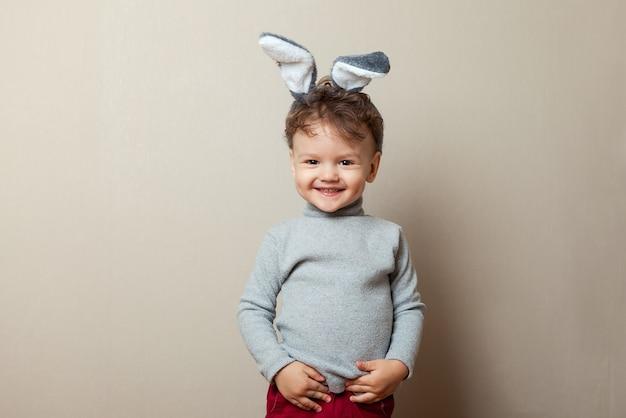 Menino bonitinho com orelhas de coelho em fundo cinza