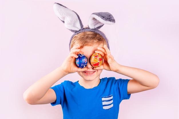 Menino bonitinho com orelhas de coelho na cabeça, fechando os olhos com ovos coloridos no fundo rosa.