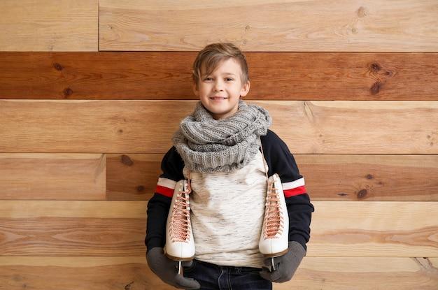 Menino bonitinho com patins de gelo contra madeira