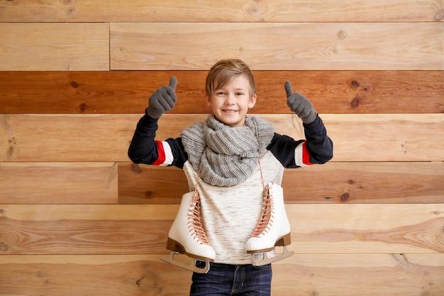Menino bonitinho com patins de gelo mostrando o polegar contra madeira