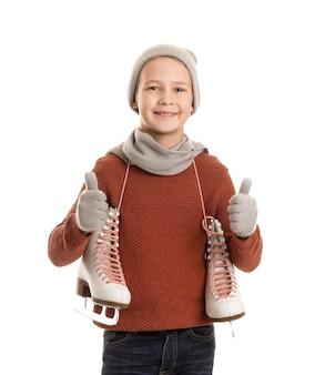Menino bonitinho com patins de gelo mostrando o polegar contra o branco