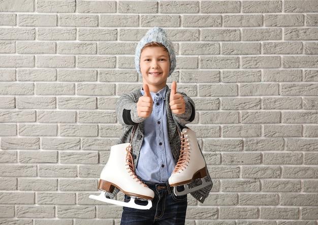 Menino bonitinho com patins de gelo mostrando o polegar para cima contra um tijolo