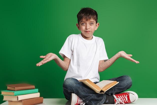 Menino bonitinho com sardas estudando, sentado com uma pilha de livros na parede verde, lendo