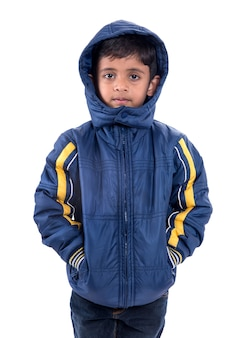 Menino bonitinho com um casaco de inverno isolado em uma parede branca