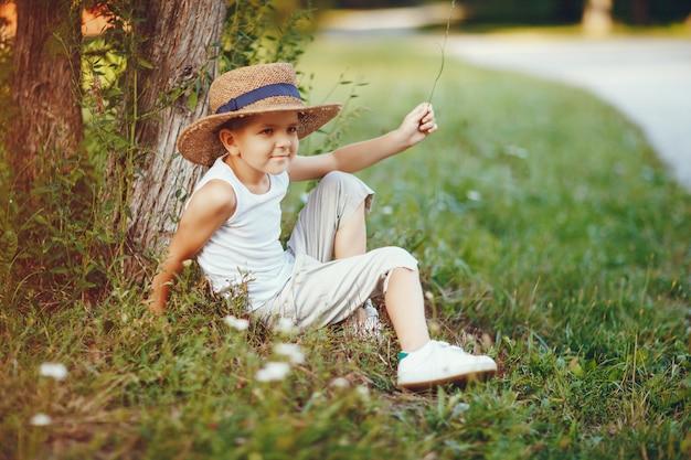 Menino bonitinho com um chapéu passando um tempo em um parque de verão