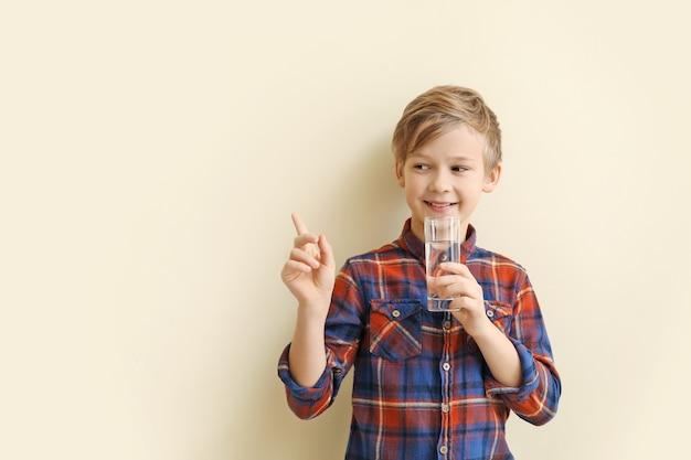 Menino bonitinho com um copo de água na cor