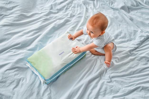 Menino bonitinho com um pacote de calcinhas de fraldas deitada na cama em casa. higiene infantil.