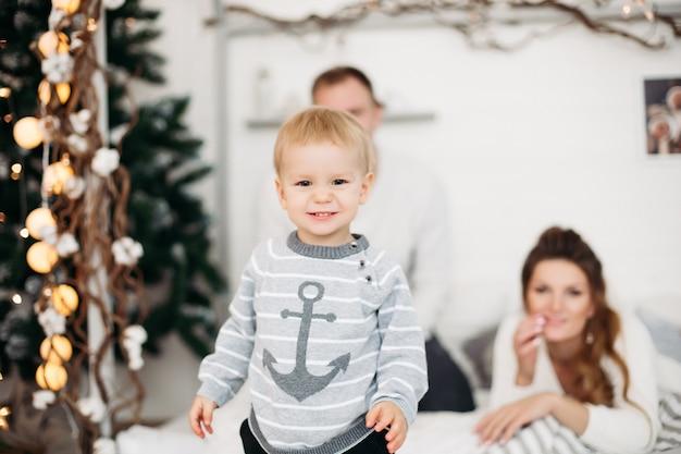 Menino bonitinho com um suéter cinza em pé no estúdio e olhando para longe com os pais jovens atrás