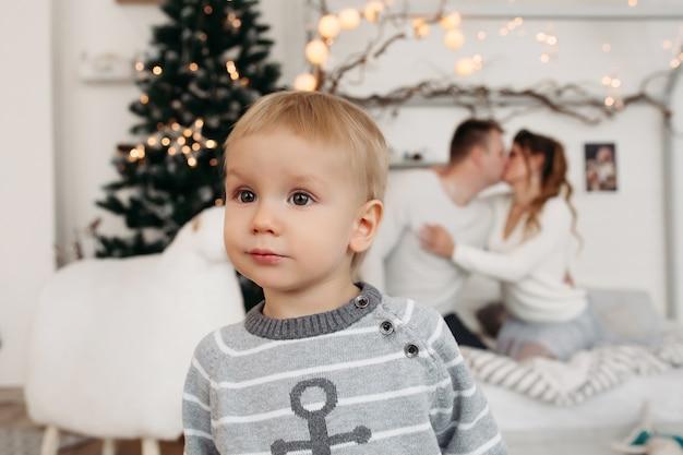 Menino bonitinho com um suéter cinza em pé no estúdio e olhando para longe, enquanto jovens pais apaixonados se abraçam e se beijam atrás