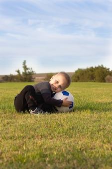 Menino bonitinho com uma bola no belo parque na natureza