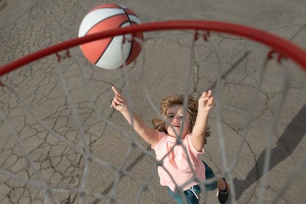 Menino bonitinho com uniforme de basquete, pulando com bola de basquete para tiro, criança feliz jogando ba ...