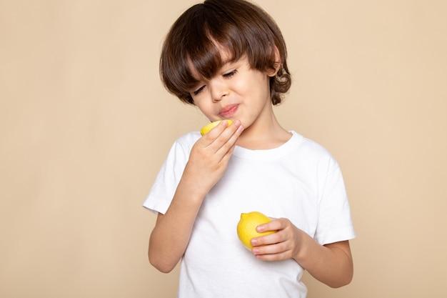 Menino bonitinho comendo limão azedo na rosa
