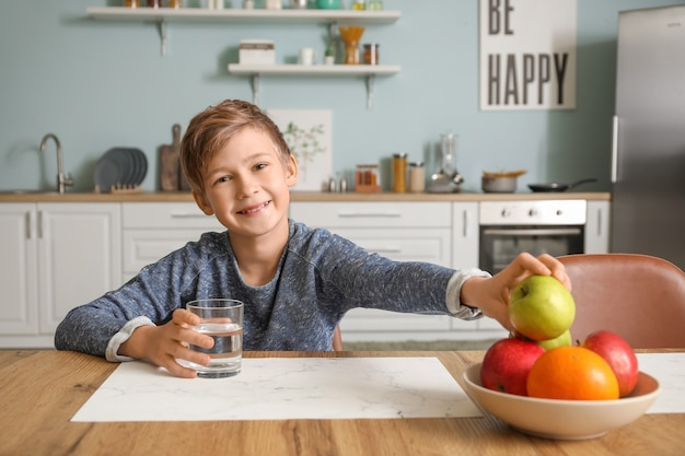 Menino bonitinho comendo maçã e bebendo água na cozinha