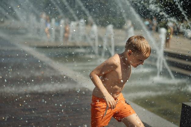 Menino bonitinho correndo em uma fonte em são petersburgo, rússia