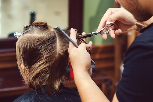 Menino bonitinho cortando cabelo de cabeleireiro na barbearia.