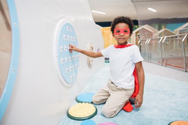 Menino bonitinho de etnia africana, com manto vermelho de super-homem e roupa casual branca, brincando no centro de lazer