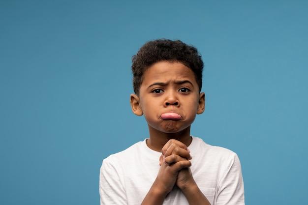 Menino bonitinho de etnia africana segurando as mãos pelo queixo com uma expressão suplicante em pé no azul