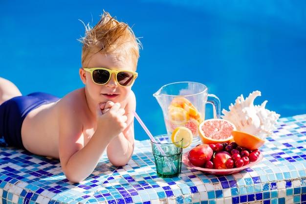 Menino bonitinho de óculos escuros e maiô bebe limonada à beira da piscina.
