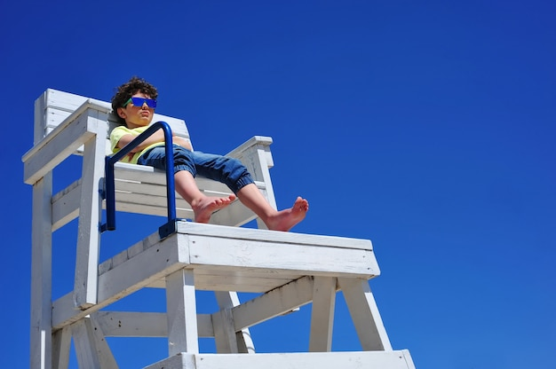 Menino bonitinho de óculos escuros sentado em uma torre de salva-vidas na praia