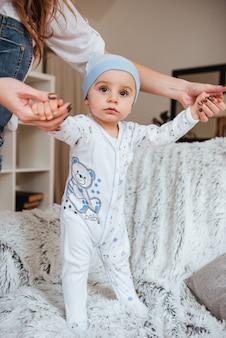Menino bonitinho de pé no sofá e de mãos dadas com a mãe em casa