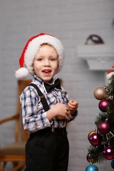 Menino bonitinho decora uma árvore de natal no interior com enfeites de natal