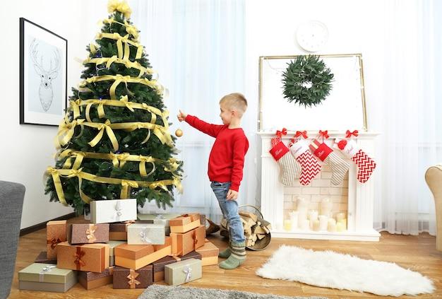 Menino bonitinho decorando a árvore de natal em casa
